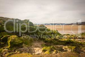 sandy beach with low tide puddles and rocky foreground interest and sand patterns and texture