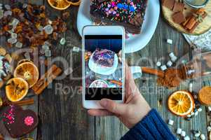 White smartphone in a woman's hand takes a piece of cake and swe
