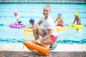 Portrait of female lifeguard holding rescue can at poolside