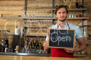 Barista holding open signboard in coffee shop