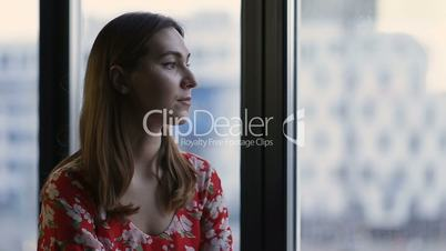 Pensive woman's profile looking out of the window