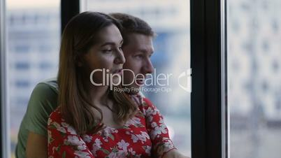 Peaceful young couple looking through the window