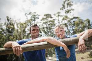 Smiling man and woman leaning on a hurdle during obstacle course