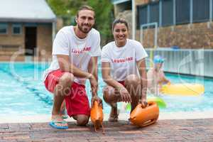 Male and female lifeguards holding rescue cans at poolside