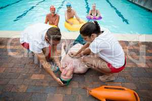 Rescue workers helping unconscious senior man at poolside