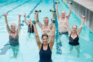 Happy senior swimmers with trainer during weightlifting training in swimming pool