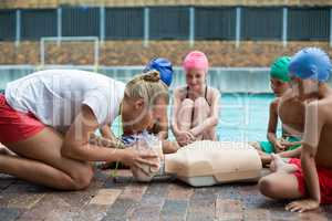 Female lifeguard demonstrating children during rescue training