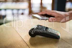Customer paying through smart phone in coffee shop