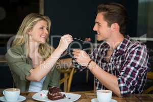 Smiling couple feeding each other dessert in cafe