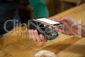 Barista accepting payment through smart phone in coffee shop