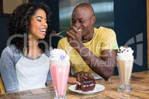 Man feeding dessert to woman in coffee shop