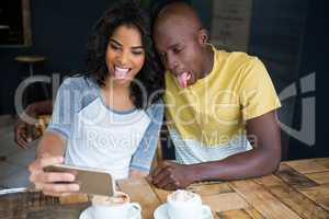 Couple making faces while taking selfie in coffee shop