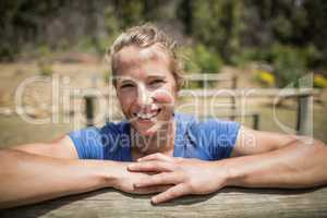 Smiling woman leaning on a hurdle during obstacle course