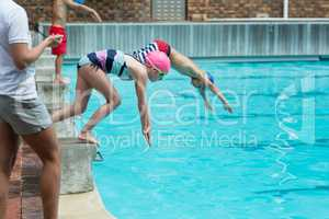 Female instructor monitoring time of children diving in pool