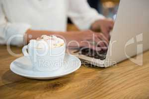 Woman using laptop by coffee with froth on table in cafe
