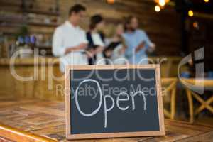 Open signboard with customers in background at coffee shop
