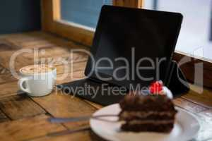 Digital tablet with pastry and coffee cup on table
