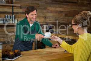 Barista serving coffee to female customer in cafe
