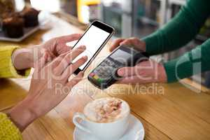 Barista accepting payment through smart phone