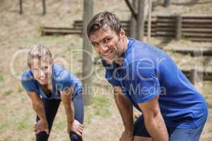 Tired man and woman bend down with hands on knees during obstacle course