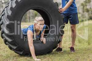 Woman crawling through the tire during obstacle course