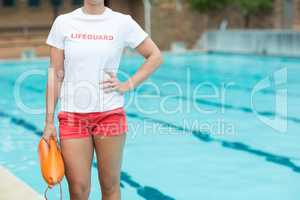 Female lifeguard holding rescue can at poolside