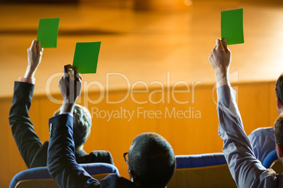 Rear view of business executives show their approval by raising hands