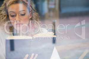 Beautiful woman reading book seen through cafe window