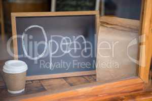 Open signboard with disposable coffee cup and paper bag in cafe