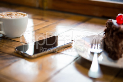 Smart phone with pastry and coffee cup on table