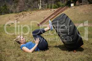 Fit woman performing leg workout with tier during obstacle course