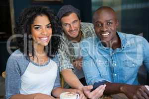 Male and female friends with mobile phone in coffee shop