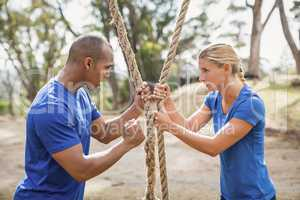 Male trainer assisting woman in rope climbing during obstacle course