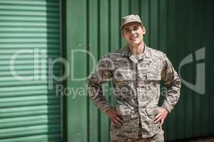 Portrait of smiling military soldier standing with hands on hip