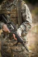 Mid section of military soldier holding a rifle