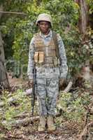 Portrait of confident military soldier standing with rifle