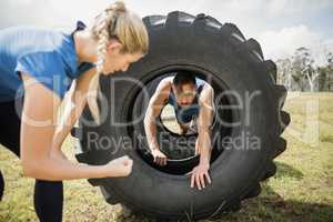 Man crawling through the tire during obstacle course while trainer cheering