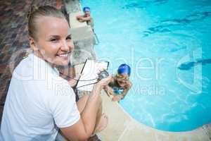 Instructor monitoring time of children swimming in pool