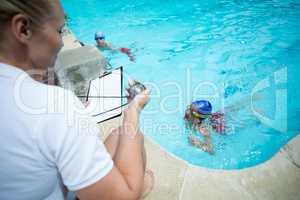 Female instructor monitoring time of children swimming in pool