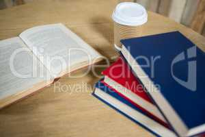 Books and disposable coffee cup on table in cafe
