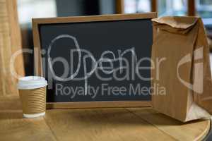 Open signboard with disposable coffee cup and paper bag on table