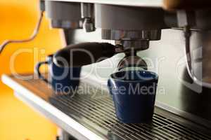 Machine making cup of coffee in cafe