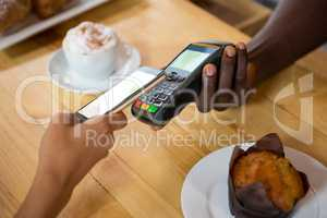 Barista accepting payment through mobile phone at cafe