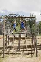 Fit man and woman climbing down the rope during obstacle course