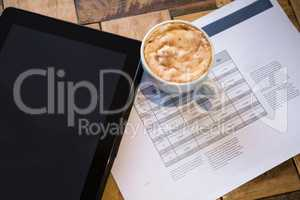 Digital tablet with coffee and document on table