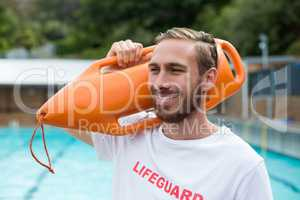 Male lifeguard carrying rescue can at poolside