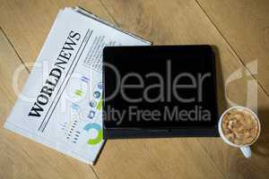 Digital tablet with coffee and newspaper on table in cafe