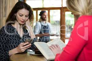 Young women using phone and reading book in coffee shop