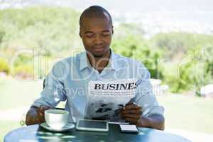 Man reading business newspaper at restaurant
