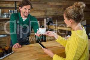 Barista serving coffee to female customer in cafeteria